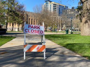 """a sign in front of a park reads """"Park Closed"""""""