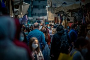 a woman stands in a crowd with a mask over her mouth and nose