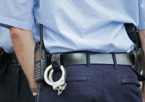 a police officer with handcuffs hanging from his belt