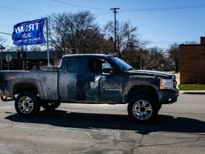 "A truck flying a ""Trump 2020"" flag"