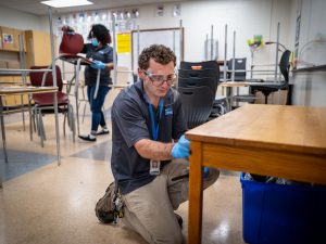 People sanitizing desks and chairs in a classroom