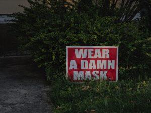 """a yard sign reads """"Wear a damn mask"""""""