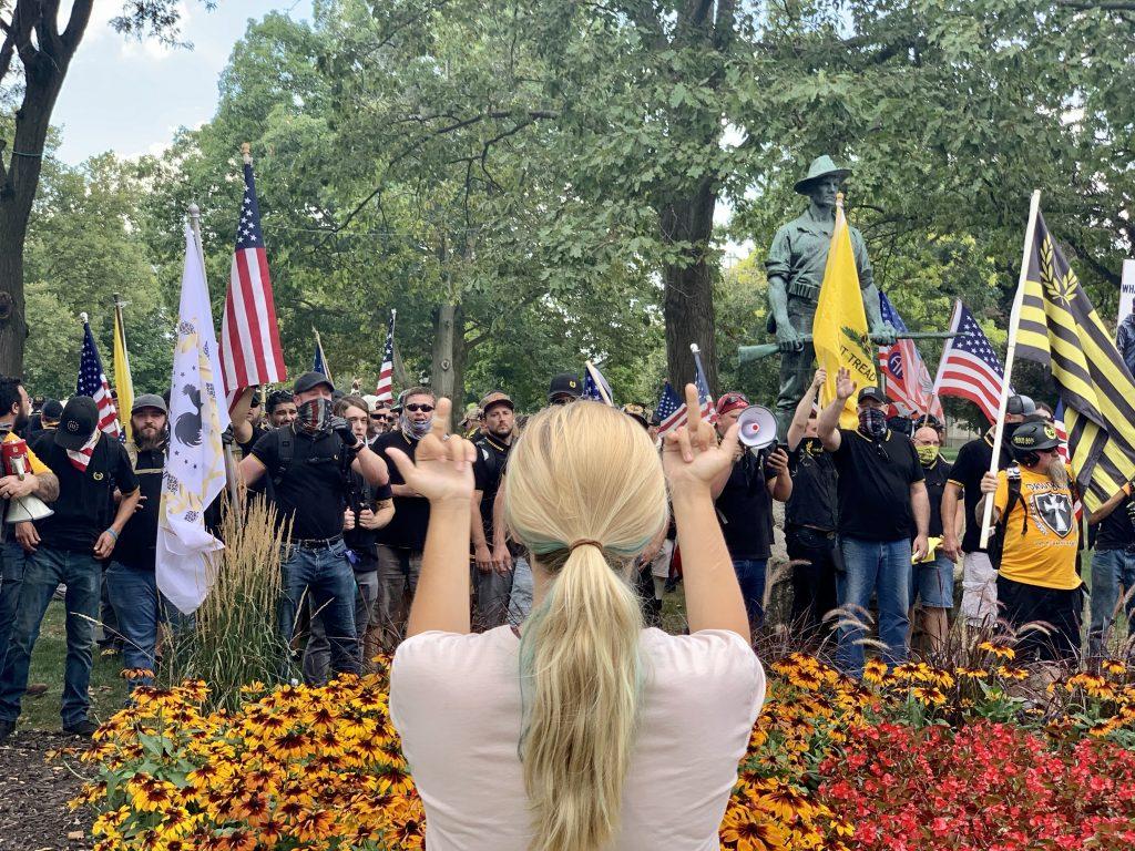 women flipping off a crowd of proud boys