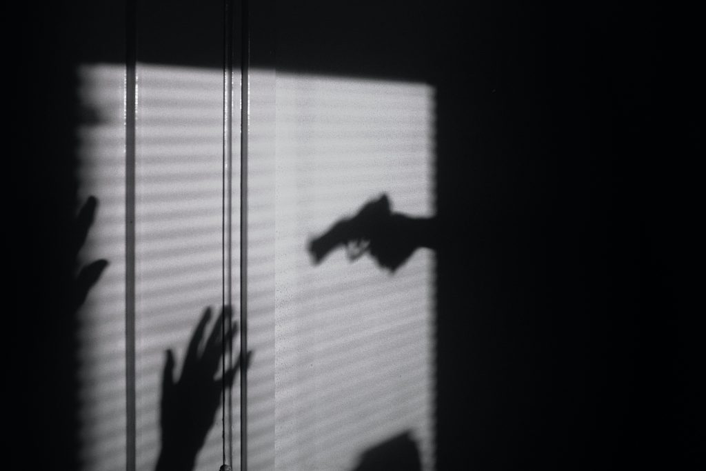 a shadow of a person pointing a gun at another person
