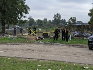 police officers stand in front of wire fencing and caution tape around a homeless encampment