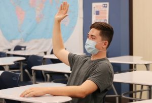 A student wearing a face mask raises his hand